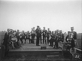 [Wolfe Island Band Performing on a Wooden Stage in a Field]